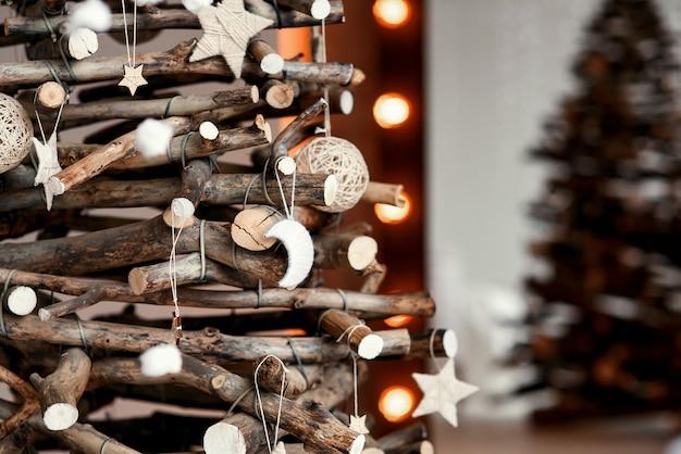 Houten decoratieve chrismas-boom met met de hand gemaakt speelgoed. stijlvol kerstinterieur ingericht in rustieke stijl.