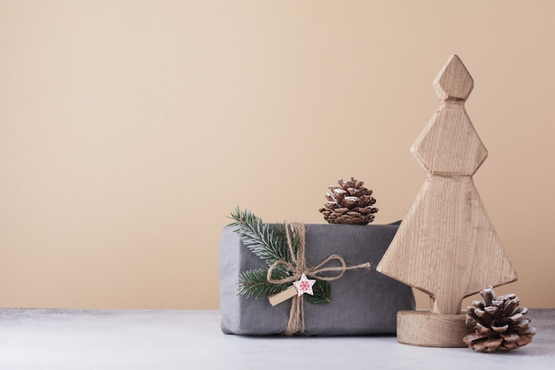 Houten decoratieve kerstboom, kegel en in stof verpakte geschenken