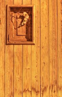 Houten deur met een klein raam, met een hart met bloemen erin