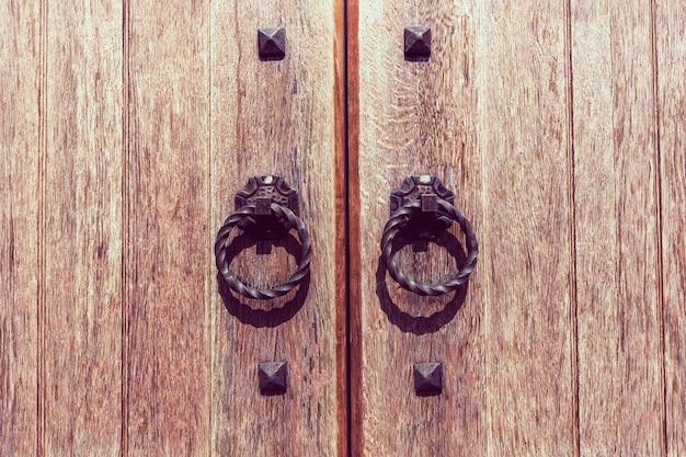 Houten deurpoort met een gesmede handgreepring