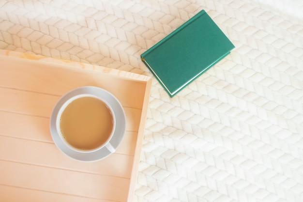 Houten dienblad, een kopje koffie met melk en een groen boek op een lichte deken