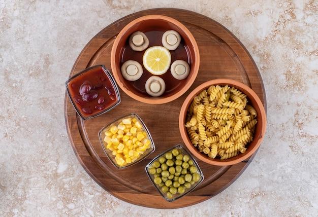Houten dienblad met een kom gekookte pasta en porties van verschillende toppings op marmeren oppervlak