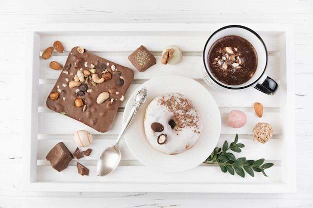 Houten dienblad met ontbijt en assortiment van chocolade