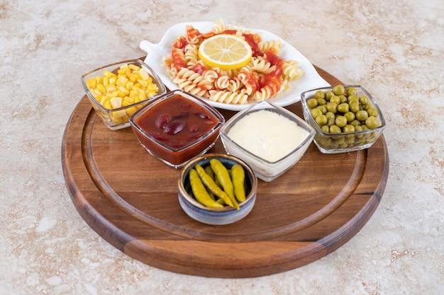 Houten dienblad met pasta serveren en kommen met toppings en dressings op marmeren oppervlak.