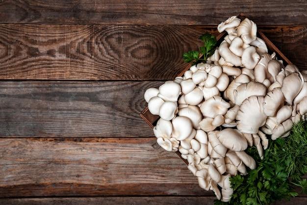Houten dienblad met rauwe oesterzwammen op houten tafel