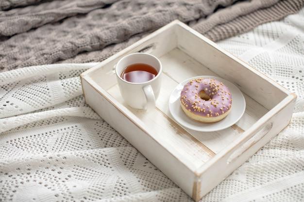 Houten dienblad met thee en gediende doughnut