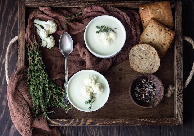 Houten dienblad met twee keramische kom met bloemkool roomsoep garneer met verse bloemkool, tijm en brood. herfst- of wintercomfortvoedsel.