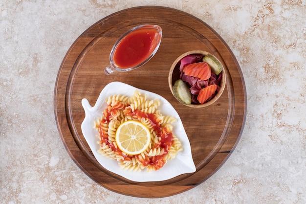 Houten dienblad onder een schotel van gekookte pasta, ketchup en een kom gemengde augurken op marmeren oppervlak.