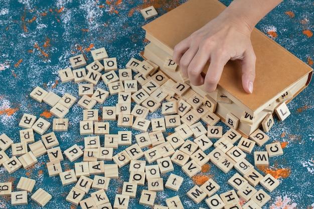 Houten dobbelstenen met letters erop tussen boekpagina's.