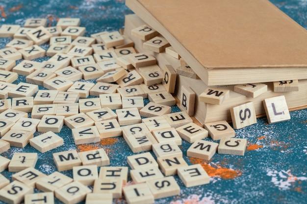 Houten dobbelstenen met letters erop tussen de pagina's van een boek.