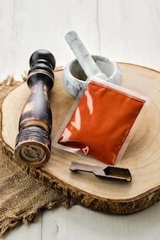 Houten doorsnede met gerookte paprika in plastic verpakking en stenen vijzel en molen
