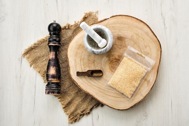 Houten doorsnede met knoflook in plastic verpakking en stenen vijzel en molen
