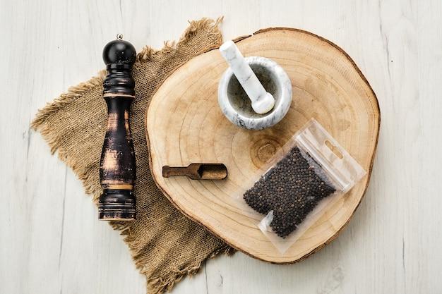 Houten doorsnede met peperkorrels in plastic verpakking en stenen vijzel en molen