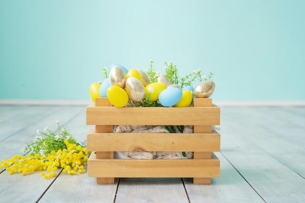 Houten doos met blauwe, gele en gouden paaseieren tegen een blauwe muur