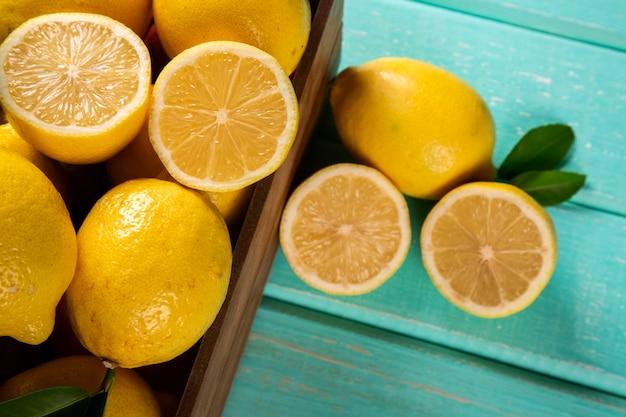 Houten doos met citroenen op groene houten achtergrond