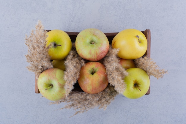 Houten doos met verse groene appels op stenen tafel.