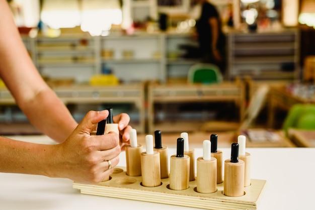 Houten drukknoppen in een montessorieklas gepulseerd door de leraar