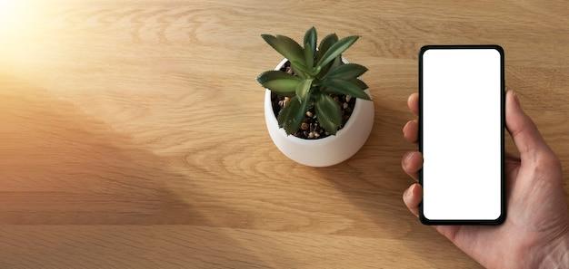 Houten eco-banner met scherm van mobiele telefoon voor mock-up in mannenhand en groene kamerplant in pot. app op smartphone-advertentie.