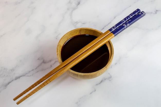 Houten eetstokje gebruiksvoorwerp voor het eten van oosterse gerechten op een kom met sojasaus