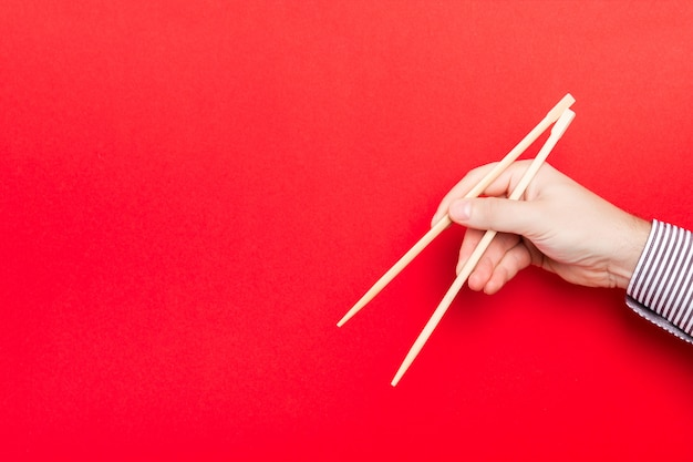 Houten eetstokjes holded met mannelijke handen op rode achtergrond
