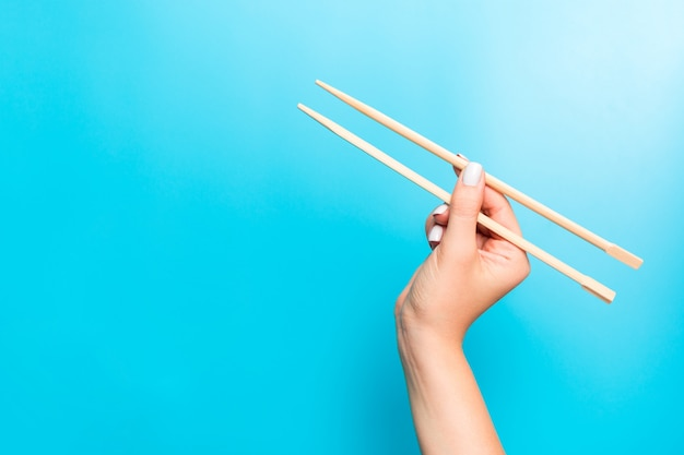 Houten eetstokjes holded met vrouwelijke handen op blauw. klaar voor het eten van s met lege ruimte