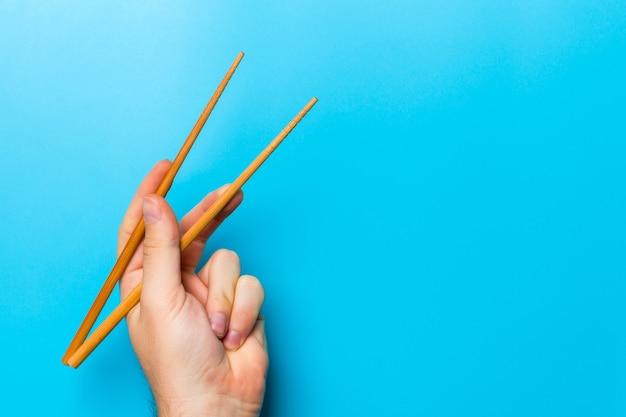 Houten eetstokjes in mannenhand op zwarte achtergrond met lege ruimte voor uw idee. lekker eten concept.