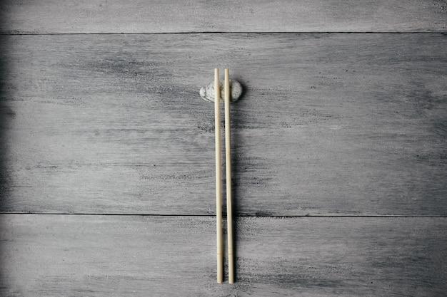 Houten eetstokjes voor chinees aziatisch voedsel op lichte houten achtergrond en steen hoogste mening
