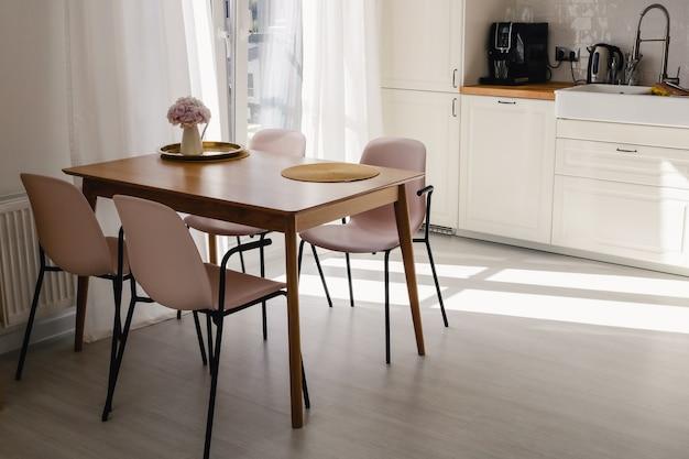 Houten eettafel met vier roze plastic stoelen eromheen en een roze bloem erop in een moderne keuken op een zonnige dag