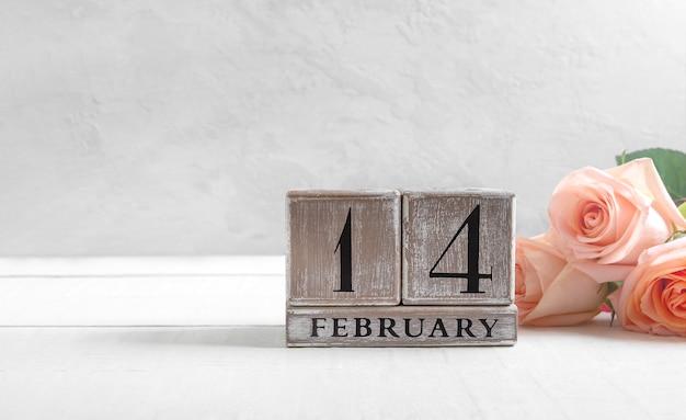 Houten eeuwigdurende kalender op 14 februari, boeket rozen, valentijnsdag.