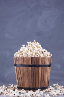 Houten emmer met gezouten witte popcorn boven stenen tafel