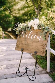 Houten ezel met inscriptie in een mooie gesmede metalen standaard versierd met witte rozen op de