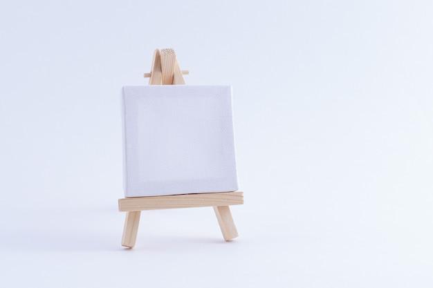 Houten ezelminiatuur met leeg wit vierkant canvas