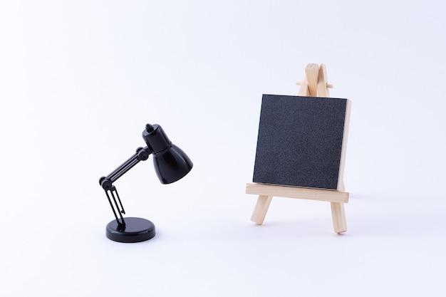 Houten ezelminiatuur met leeg zwart vierkant canvas en tafellamp