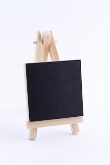Houten ezelminiatuur met leeg zwart vierkant canvas voor kunstenaars en schilders