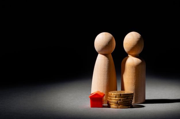 Houten familie met speelgoed huis en stapel munten. besparingen voor huisaankoopconcept