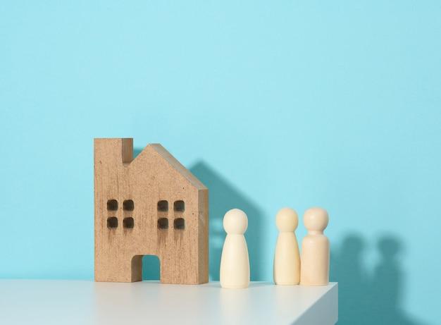 Houten familiebeeldjes, modelhuis op een blauwe achtergrond. aankoop van onroerend goed, verhuurconcept. verhuizen naar nieuwe appartementen