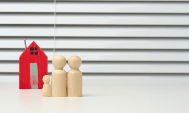 Houten familiebeeldjes, modelhuis op een bruine achtergrond. aankoop van onroerend goed, verhuurconcept. verhuizen naar nieuwe appartementen