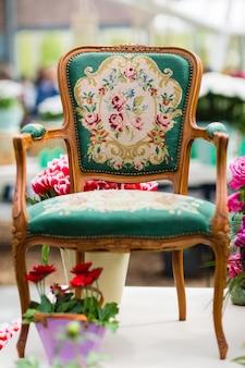 Houten fauteuil met stoffen bekleding en bloemen op de achtergrond