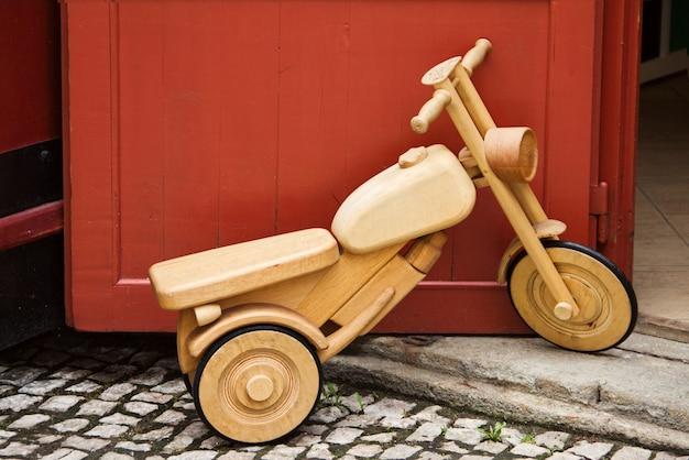 Houten fiets speelgoed staat naast een rode deur