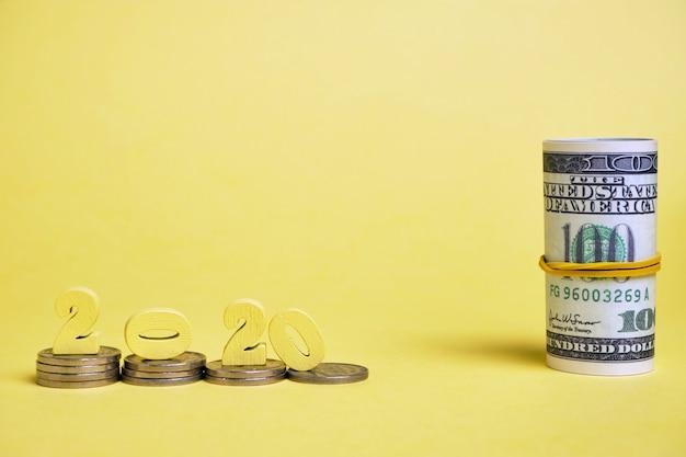 Houten figuren 2020 op stapels munten in de buurt van een rol dollars gebonden met een elastische band achtergrond