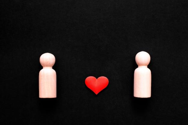 Houten figuren die twee homoseksuele mannen voorstellen, verliefd, met hart.