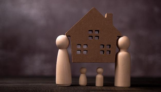 Houten figuren familie staande en draag houten huis om de problemen te beschermen en te belasten om de familie te beschermen.