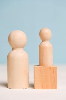 Houten figuren met een kubus op een blauwe achtergrond. begeleiding concept. een professional leert een student. detailopname.