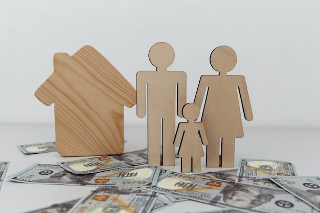 Houten figuren van familie met huisaankoop of verkoopconcept