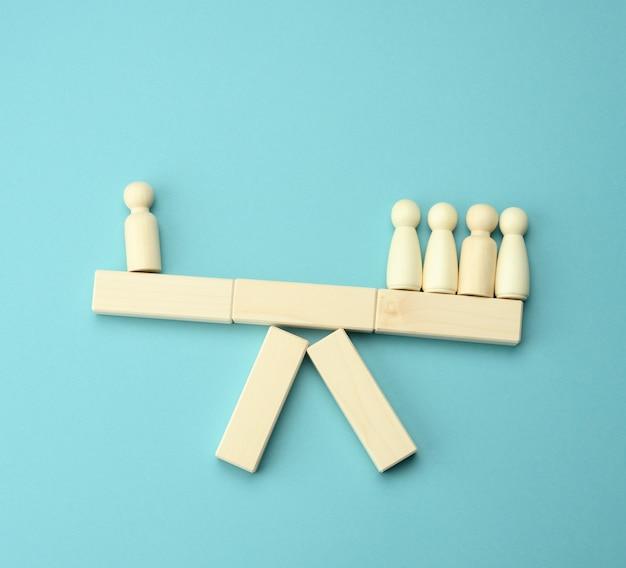 Houten figuren van mannen op een schommel, de groep weegt zwaarder dan de eenling. het concept van belangenverstrengeling, haten. alleen de groep confronteren
