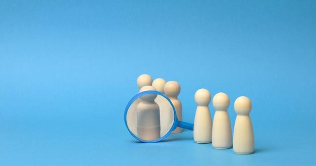 Houten figuren van mannen staan op een blauwe achtergrond en een plastic vergrootglas. wervingsconcept, zoeken naar getalenteerde en capabele werknemers, carrièregroei, kopieerruimte