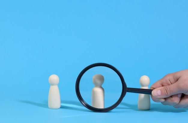 Houten figuren van mannen staan op een blauwe ondergrond en een zwart vergrootglas. wervingsconcept, zoeken naar getalenteerde en capabele medewerkers, loopbaangroei