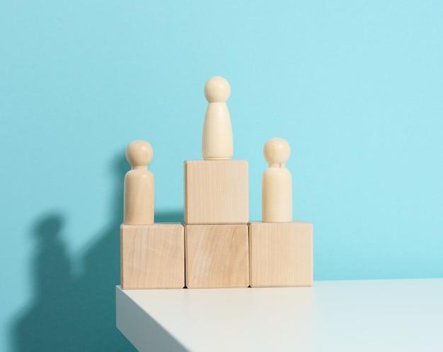 Houten figuren van mannen staan op een voetstuk van hun kubussen op een blauwe achtergrond. het concept van rivaliteit in sport, zaken en leven. succes en leiderschap behalen