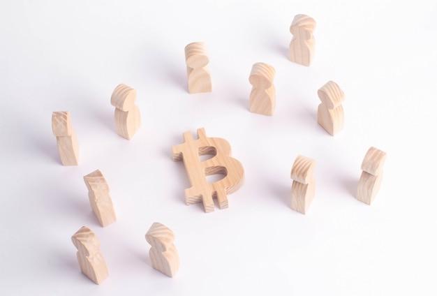 Houten figuren van mensen staan in de buurt van een bitcoin op een witte achtergrond