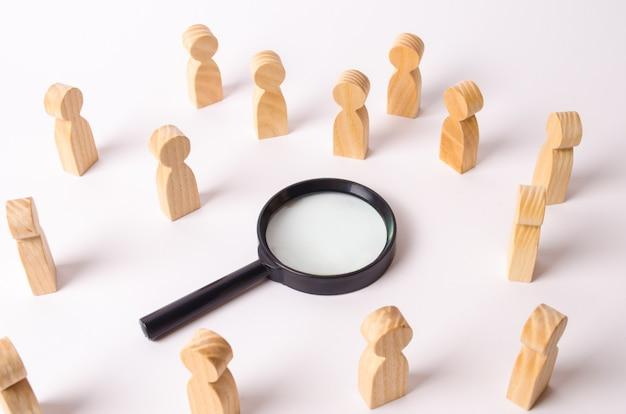Houten figuren van mensen staan rond het vergrootglas en kijken naar het midden.